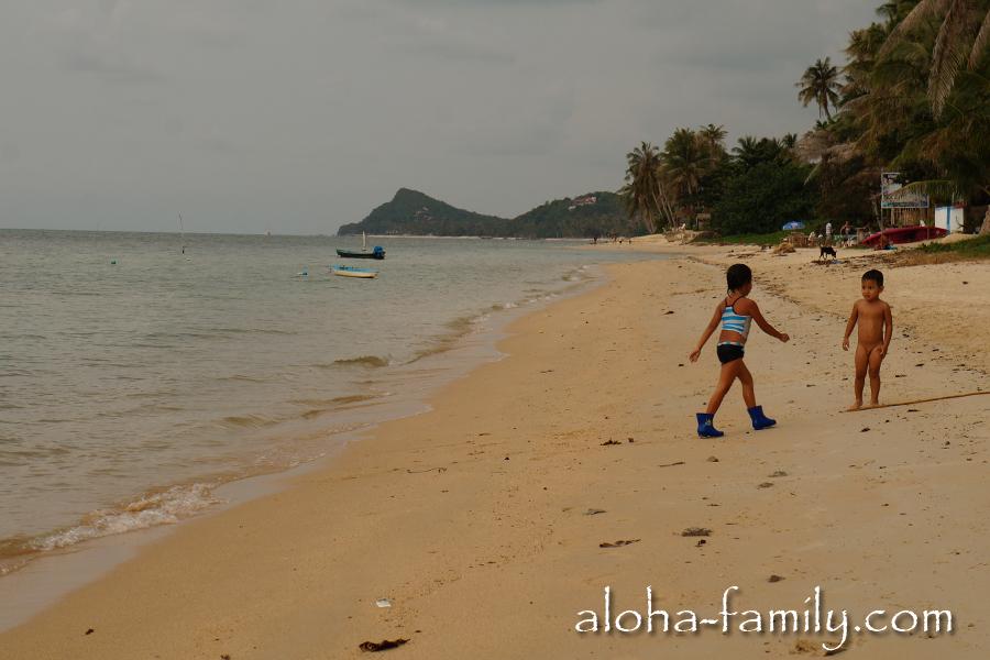Маленький голопопый таец играет с сестрой или подругой на пляже