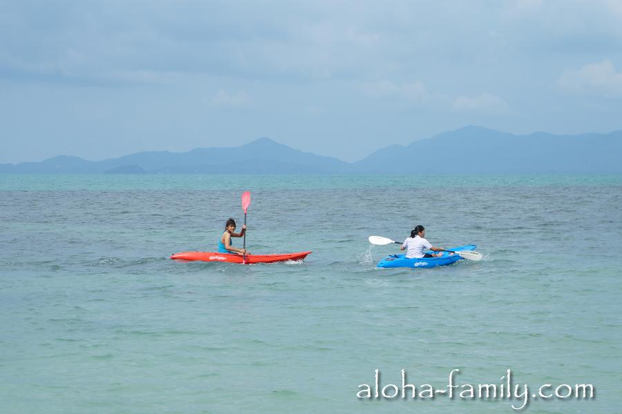 Тайские девушки занимаются греблей на фоне острова Панган