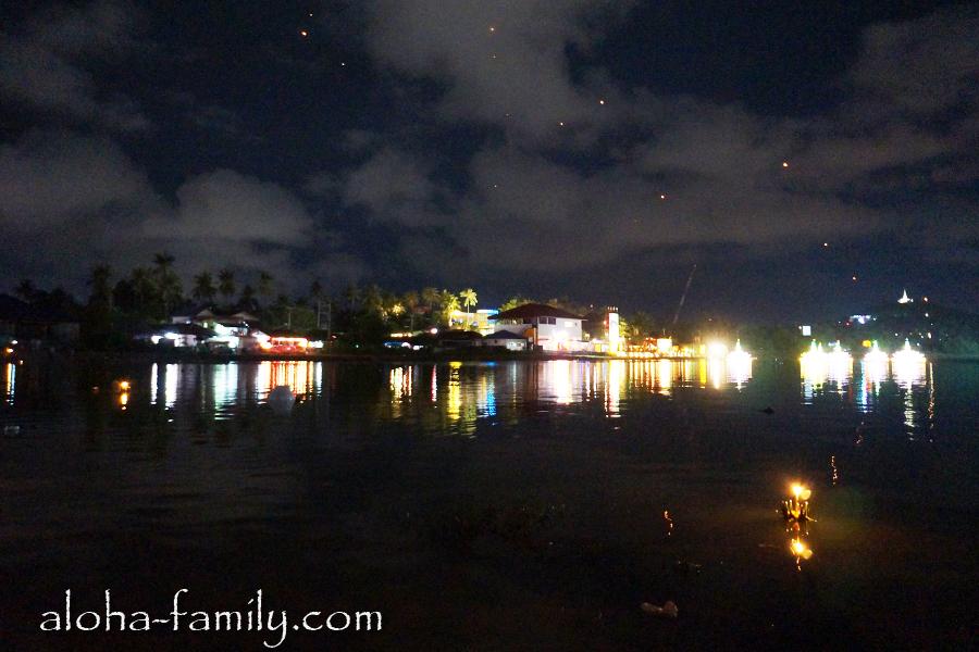 Кратонги медленно уплывают в даль на фоне улетающих небесных фонариков