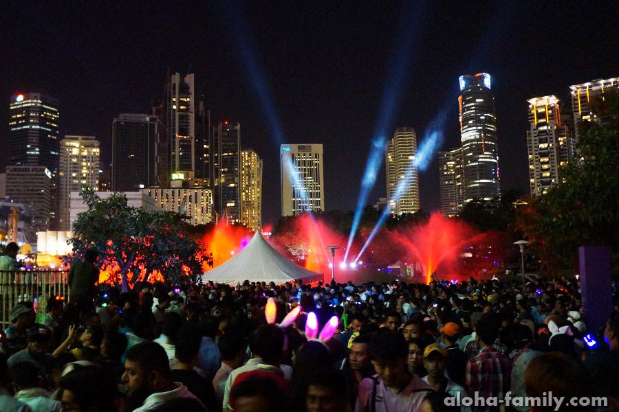 Толпа возле танцующих фонтанов в новогоднюю ночь